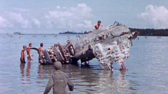 marines examining wreckage of japanese fighter plane in shallow water / guam mariana islands - guam stock videos & royalty-free footage