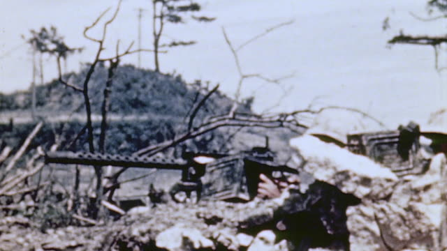 marines firing m1919 machine gun and infantrymen carrying flamethrower tanks making their way to higher ground / naha okinawa japan - infanterie stock-videos und b-roll-filmmaterial