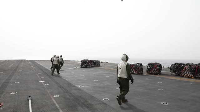 vídeos de stock, filmes e b-roll de marines from combat cargo transport mail food and parts to and from the flight deck during a routine vertical replenishment onboard the amphibious... - veículo anfíbio