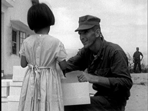 S Marines handing out toy dolls to Vietnamese girls MS smiling little girl holding box with doll / Vietnam / AUDIO