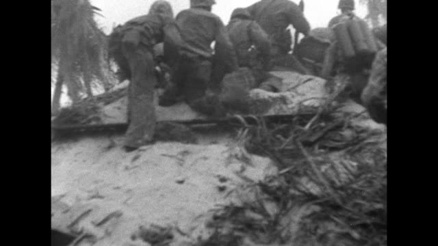 US Marines hunkered down in dugout fortified with palm tree trunks / cautious men in combat gear at steep sand emplacement with one throwing a...