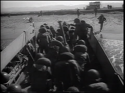 marines in battle gear exiting landing craft + running onto beach / vietnam - ベトナム戦争点の映像素材/bロール
