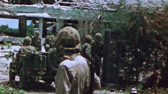 s marines in jeep driving dirt road past bombed out structure and sentries during world war ii / iwo jima japan - ジープ点の映像素材/bロール