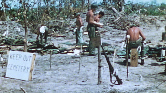 s marines in jungle camp at rest and relaxation sitting on crate walking around camp with rifle leaning against stake during world war ii / iwo jima... - battle of iwo jima stock videos and b-roll footage