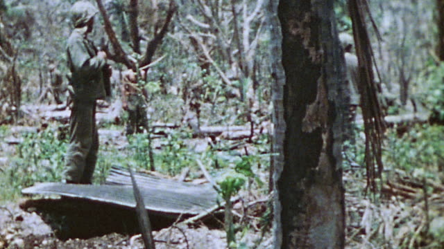 vídeos de stock, filmes e b-roll de s marines in jungle camp lying on ground during lookout watch walking around mangled jungle crouched before large stack of closed sacks and observing... - guerra do pacífico