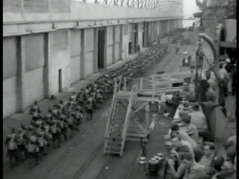 marines in line marching on dock, ship fg. soldiers, dock workers, crane lifting light tank m2a4, ship. armored tank being lifted. vehicles,... - 1942年点の映像素材/bロール