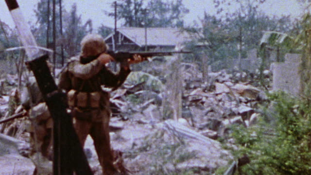 s marines in ruins of shelled village with one soldier firing m1 carbine and the other protecting his flank during wwii / peleliu palau  - infanterie stock-videos und b-roll-filmmaterial