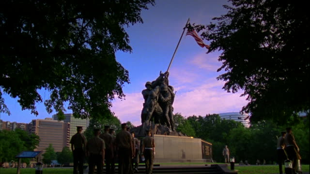 Marines in twobytwo formation dressed in short sleeve service uniforms walking up sidewalk toward United States Marine Corps War Memorial statue...