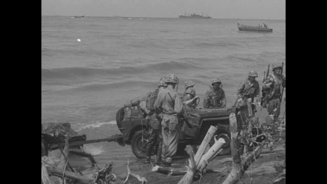 marines move ashore from higgins landing craft; a bulldozer pulling a warped wagon arrives; jeeps and artillery move on land / dozer strains to make... - 防水シート点の映像素材/bロール