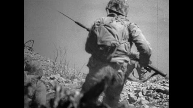 marines on beach of iwo jima climbing over hills ridges taking fire explosion in dugout trenches one soldier taking supplies from another us marines... - battle of iwo jima stock videos & royalty-free footage