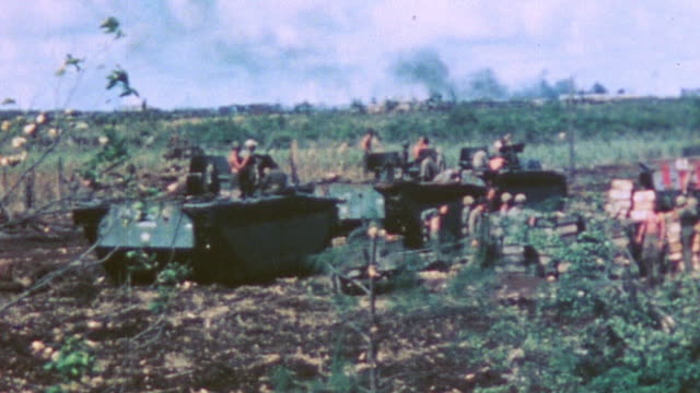 marines on ltvs driving past marines working on ground, smoke from oil fire burning in distance, marines marching in file / tinian, marina islands - amphibious vehicle stock videos & royalty-free footage