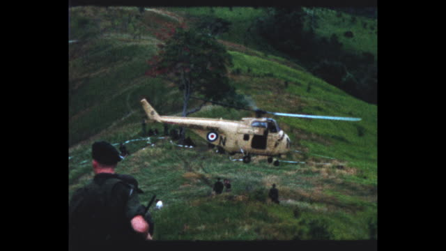 marines on verdant hillside in british north borneo, royal navy helicopter taking off and landing. from the home movie collection of jack dennis... - 英国海兵隊点の映像素材/bロール