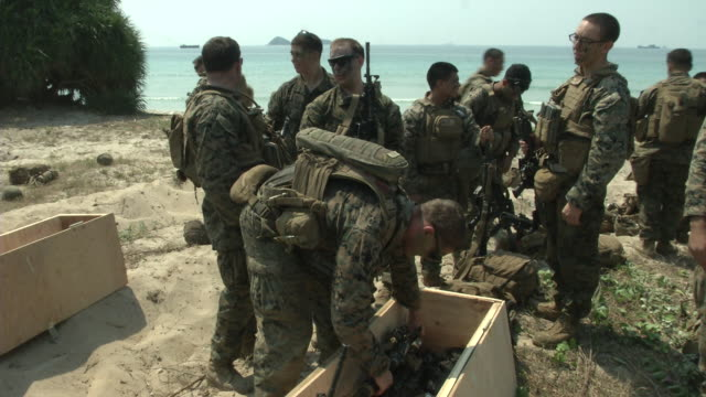 us marines pack gear on the beach head during the usthai joint military exercise titled cobra gold on hat yao beach in chonburi province eastern... - chonburi province stock videos & royalty-free footage
