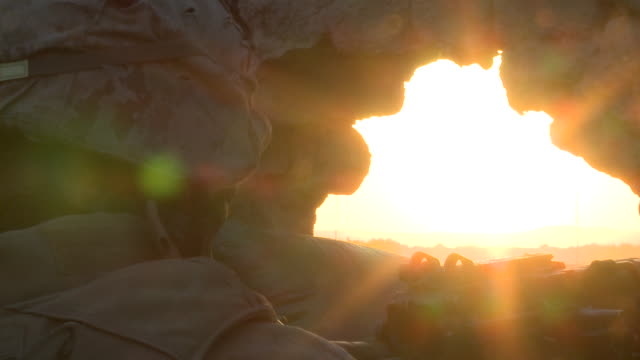 U.S. Marines peer through holes in parapets as they try to observe Taliban.