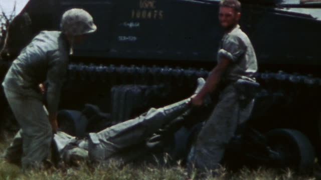 s marines recovering fallen marine from the battleground and placing his body atop a tank waiting alongside during wwii / peleliu palau  - marines stock videos & royalty-free footage