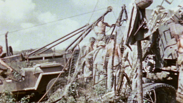 PAN Marines repairing M3 halftrack personnel carrier draped in camouflaged netting / Saipan Mariana Islands