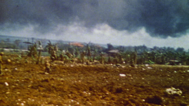 s marines resting amidst the devastation behind the front lines with plume of blue smoke in the distance / saipan mariana islands - saipan stock videos and b-roll footage
