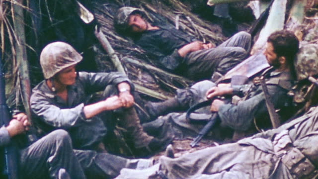 s marines resting and reclining in jungle trench while communications team is operating field radio at other end of trench during wwii pacific... - zurücklehnen stock-videos und b-roll-filmmaterial
