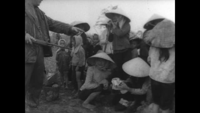 us marines round up suspected viet cong and their sympathizers outside da nang / women and children crouch on the ground surrounded by soldiers with... - ダナン点の映像素材/bロール