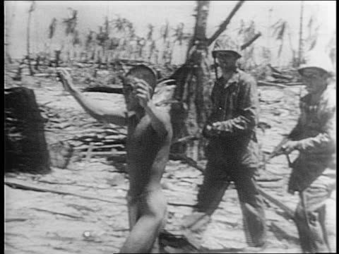 Marines slowly approach a hidden Japanese pill box on shore / soldier throws grenade at pill box / soldiers approach with guns drawn / dead Japanese...