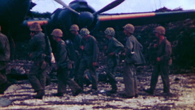 marines stopping to examine destroyed japanese twinengine aircraft another marine crossing captured airfield on bicycle and lvt passing - 装甲車点の映像素材/bロール