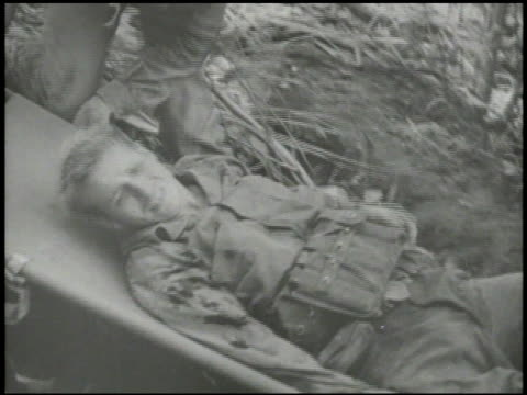 stockvideo's en b-roll-footage met s marines transporting wounded soldier on stretcher down hill other injured soldiers being helped into medical tent dead soldier on stretcher wwii... - triage