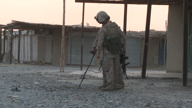 U.S. Marines use a metal detector as they check for IEDs.