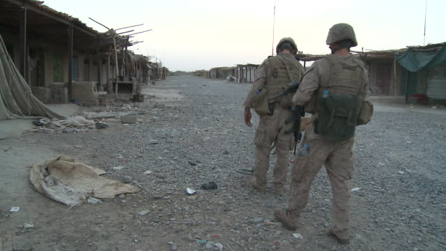 U.S. Marines use a mine detector to sweep for IEDs in an empty village street.