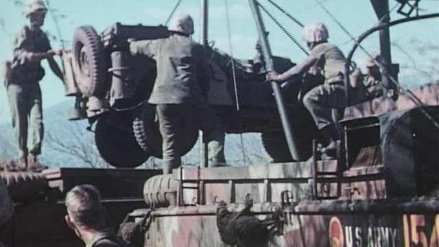 marines using a crane to unload a jeep from a dukw during world war ii pacific island invasion - 硫黄島の戦い点の映像素材/bロール