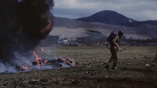 vídeos de stock e filmes b-roll de marines using flamethrowers and grenades to burn out and destroy buried enemy pillboxes, with huge clouds of black smoke and orange flames, during... - pacific war