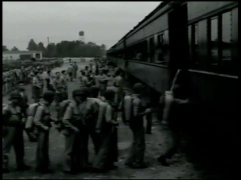 marines w/ gear boarding train. soldiers lined up by transport train. soldiers climbing on. officer talking to station master . solders w/ backpacks... - 1942 stock videos & royalty-free footage