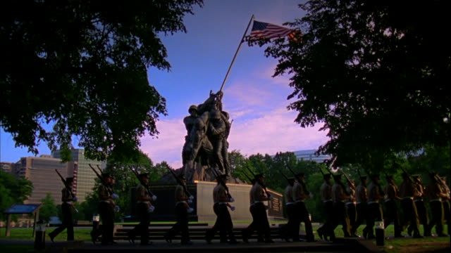 Marines w/ shouldered rifles dressed in short sleeve service uniforms walking in formation in front of United States Marine Corps War Memorial statue...