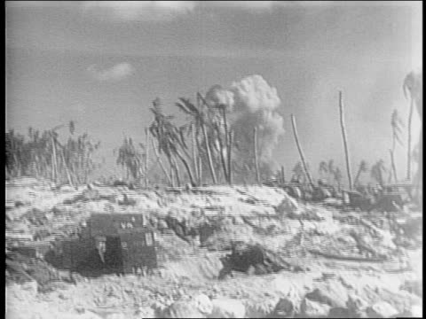 marines walk over dead japanese soldier / wreckage of the battle / marines watch for snipers/explosion in palm trees/ shells piled up on the... - militärisches landfahrzeug stock-videos und b-roll-filmmaterial