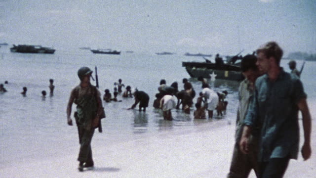 stockvideo's en b-roll-footage met marines walking along beach front while other marines guard civilians bathing in the water during wwii - leger soldaat