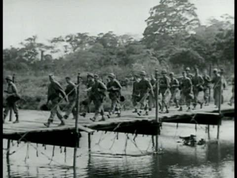 marines walking on wooden bridge walking along roadside w/ jeep passing on road. southern solomon islands world war ii wwii. - world war ii点の映像素材/bロール