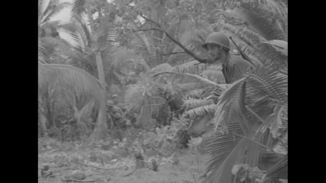 marines walking through jungle, cameraman shooting film / marines running forward firing rifles, cameraman shooting film, pan across to marines... - guam video stock e b–roll