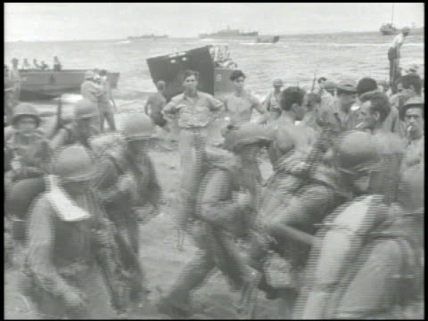 vídeos de stock e filmes b-roll de marines walking w/ gear along beach w/ us army infantry soldiers standing bg marines walking onto personnel landing craft higgins boat boats moving... - fuzileiro naval