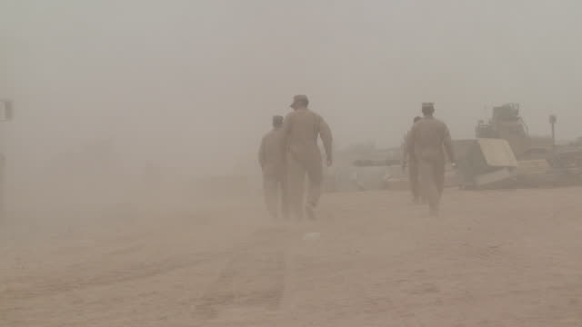 U.S. Marines wear overalls as they walk toward tents in a sandstorm.