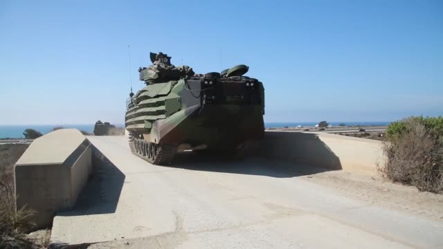 US Marines with Battalion Landing Team 3rd Battalion 1st Marine Regiment 15th Marine Expeditionary Unit use AAV7A1 Assault Amphibious Vehicles to...