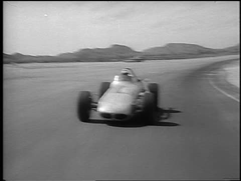 Mario Andretti testing race car towards camera on Phoenix International Raceway / newsreel