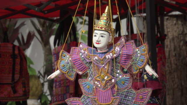 marionette turns around at wat xieng thong temple - marionette stock-videos und b-roll-filmmaterial