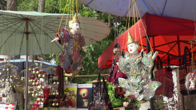 marionette turns around in souvenir shop at wat xieng thong temple - marionette stock-videos und b-roll-filmmaterial