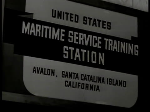 Maritime cadets walking in formation SIGN US Maritime Service Training Station VS Trainee practicing on model steering handling ship's wheel CU...