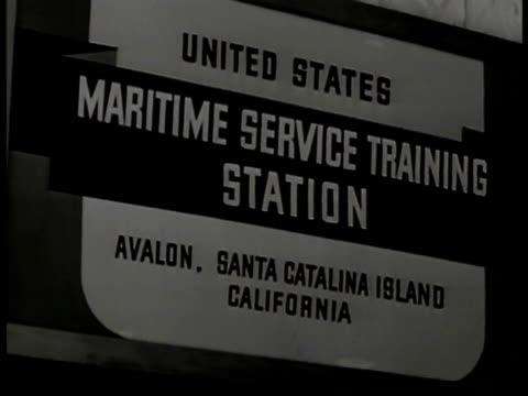 vídeos de stock, filmes e b-roll de maritime cadets walking in formation sign us maritime service training station vs trainee practicing on model steering handling ship's wheel cu... - compasso