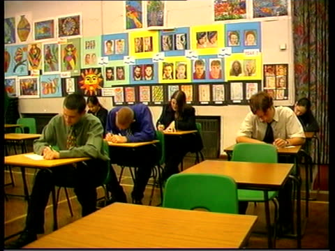 marked exam papers to be returned to pupils itn london a level pupils sitting exam in classroom ms pupils sitting exams cms boy writing on exam paper... - jungen stock-videos und b-roll-filmmaterial