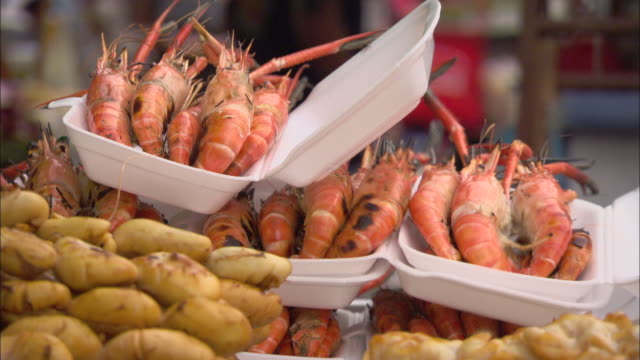 a market display in thailand features yams and shrimp. - ポリスチレン点の映像素材/bロール