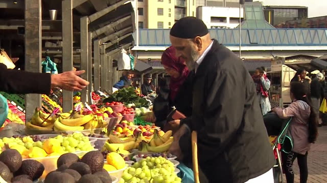 a market stall holder shouts 'any bowl a pound' as shoppers pay for fruit at a leeds market stall uk - paying stock videos & royalty-free footage