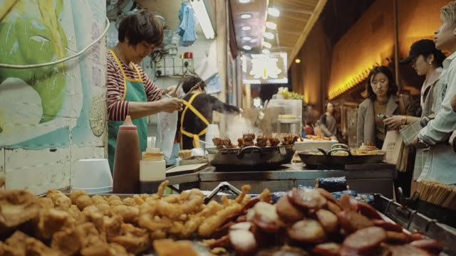 market stall selling street food, mong kok, kowloon, hong kong - retail place stock videos & royalty-free footage