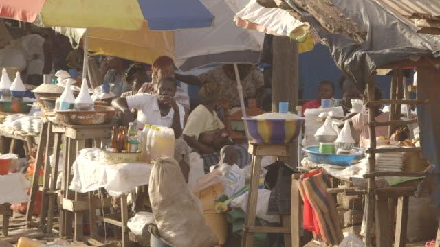 Market stallholders chat and breastfeed, Kenema, Sierra Leone.