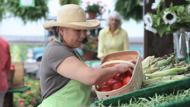 CU TU Market vendor arranging box of tomatoes at farmer's market / Richmond, Virginia, USA